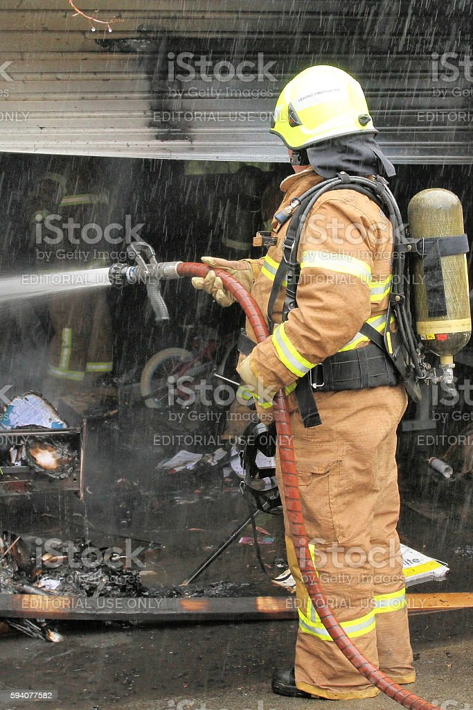Fire fighter spraying water on a garage on fire stock photo