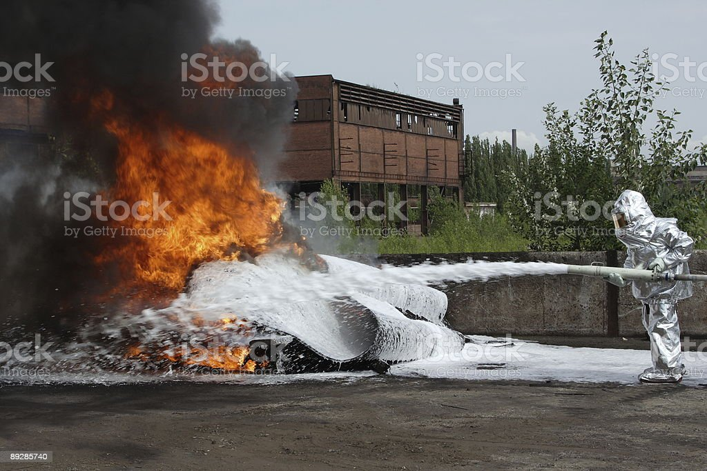 A fire fighter using a water hose to control a blaze royalty-free stock photo