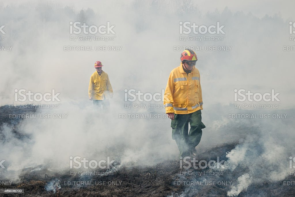Fire fighters crossing charred terrain stock photo