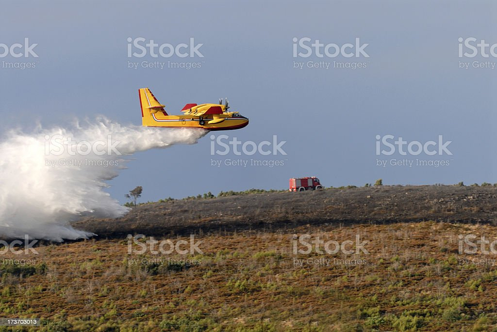 Fire fighting aircraft releases its load of water royalty-free stock photo