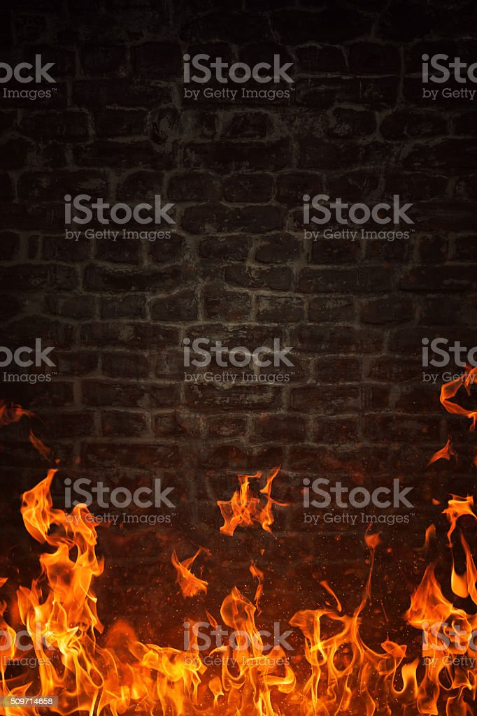 Fire flames and dark brick texture on background stock photo