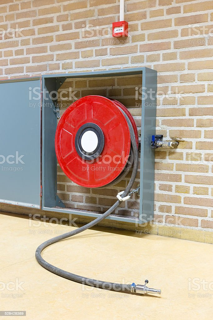 Fire hose on red reel at wall stock photo