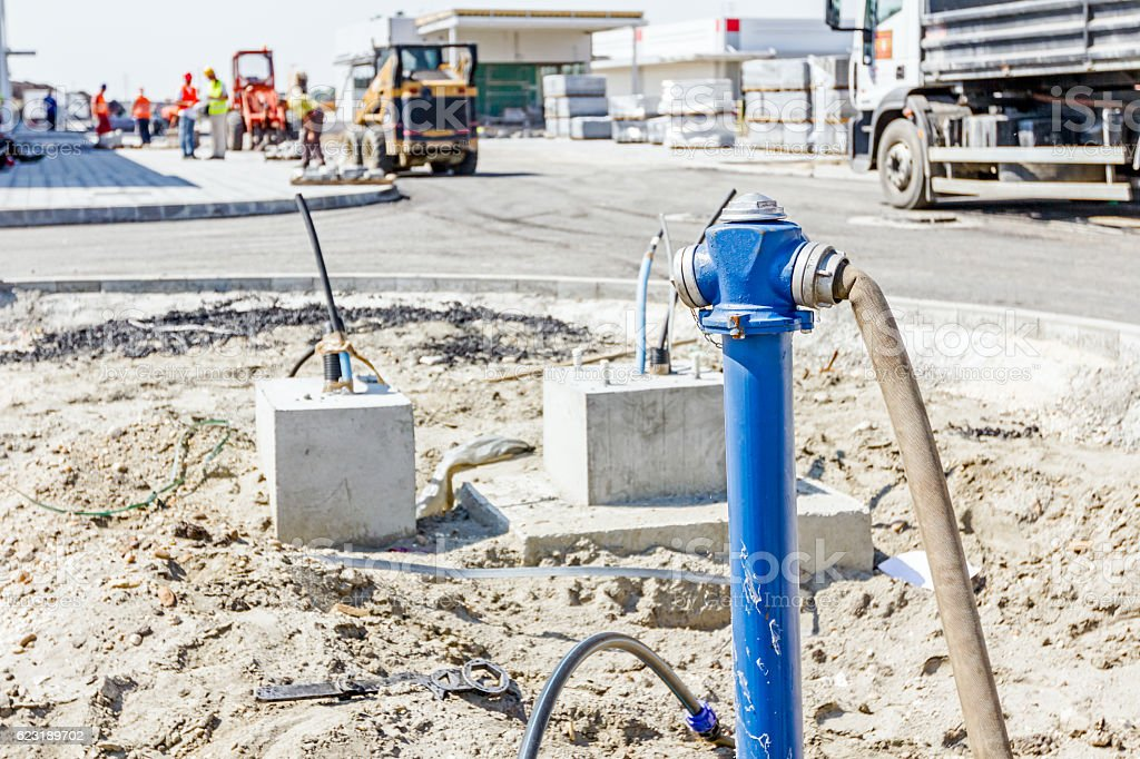 Fire hydrant with blue pipe at building site stock photo