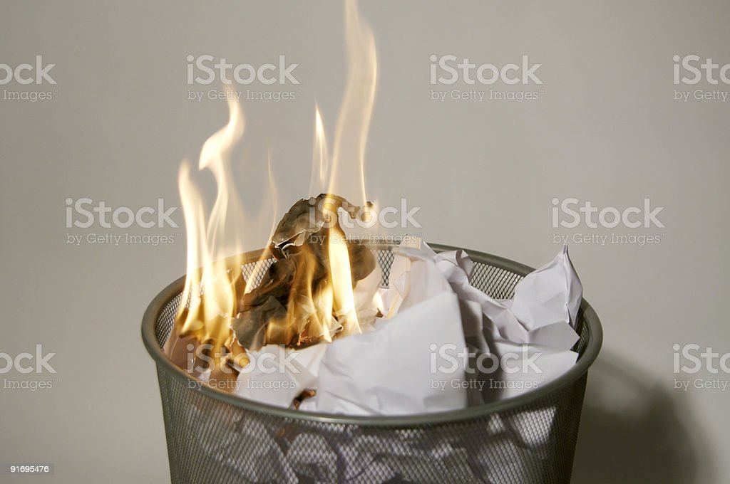 Fire in a wastepaper basket stock photo