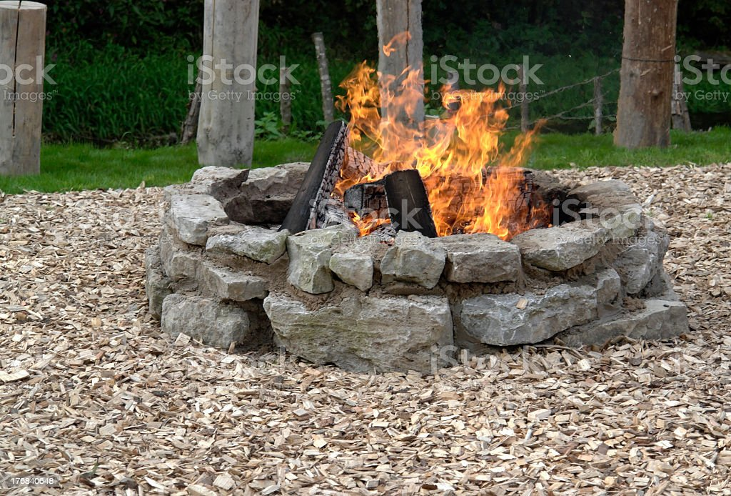 A fire in an outdoor stone fireplace  stock photo