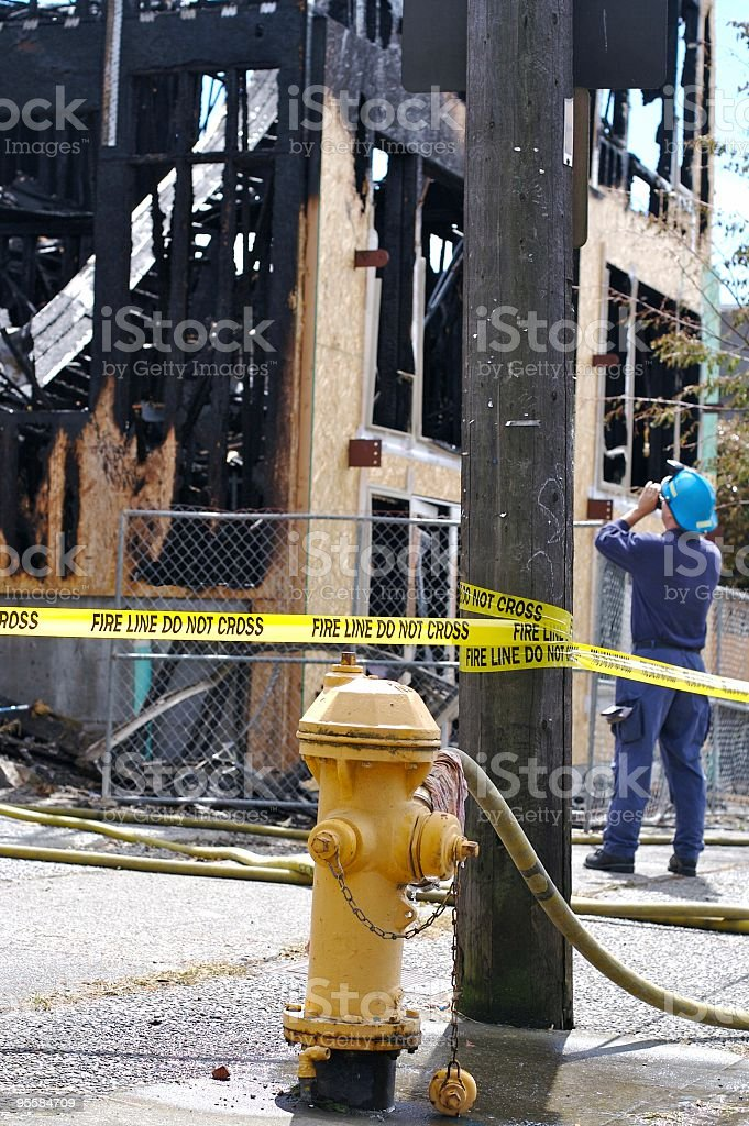 Fire inspector surveys burned out apartment complex stock photo