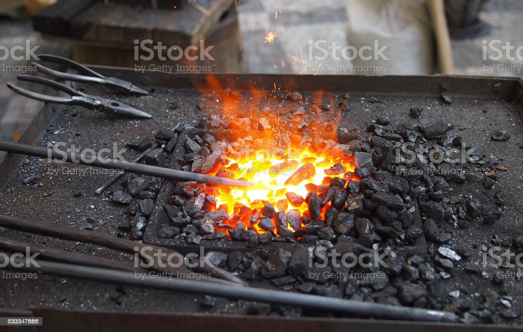 Fire, live coals and blacksmith's tools. stock photo