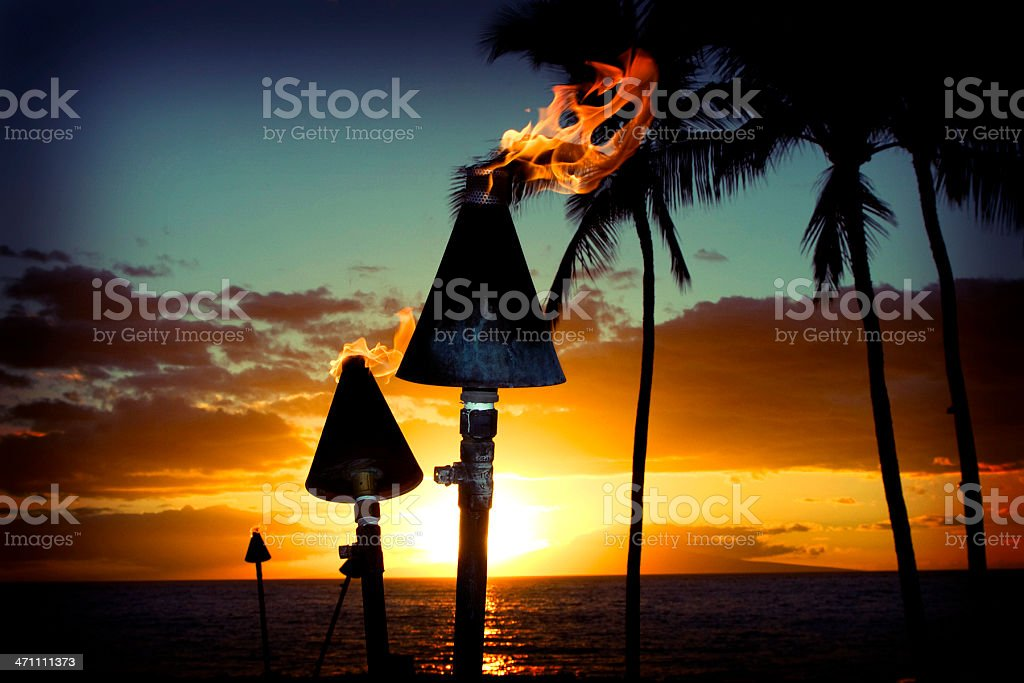 Fire torches against a beautiful island sunset stock photo