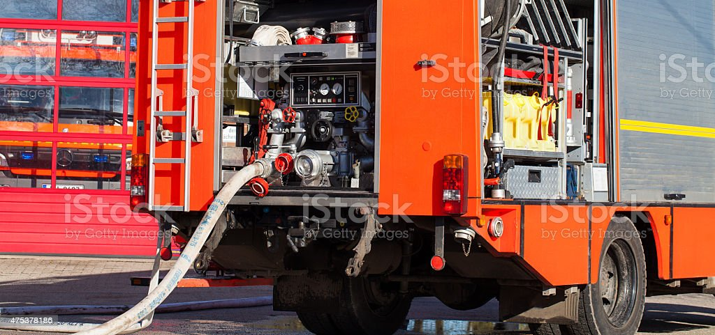 Fire truck in front of fire station with fire hose stock photo