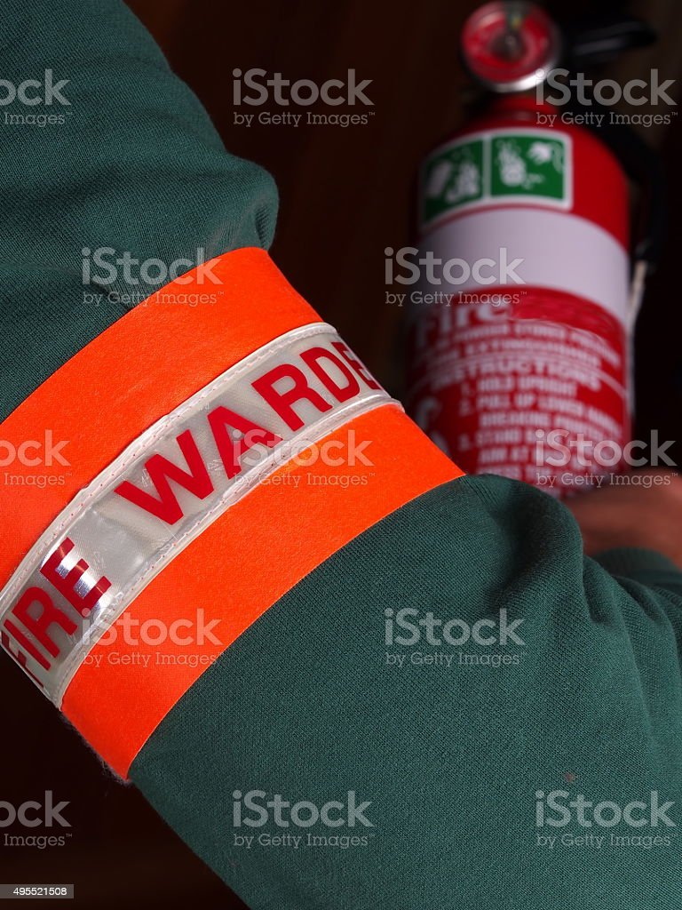 Fire warden with identification patch holding a fire extinguishe stock photo