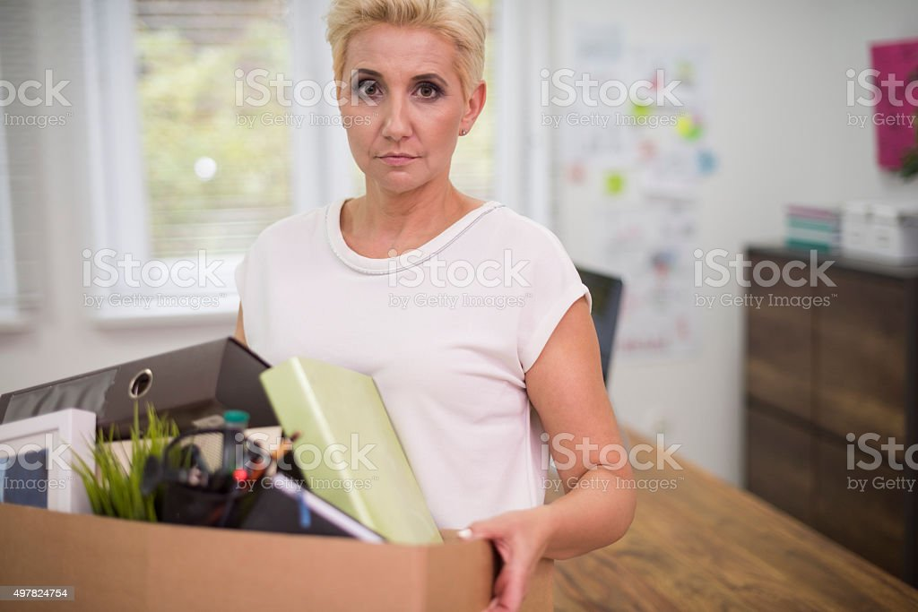 Fired woman carrying a box with some content stock photo