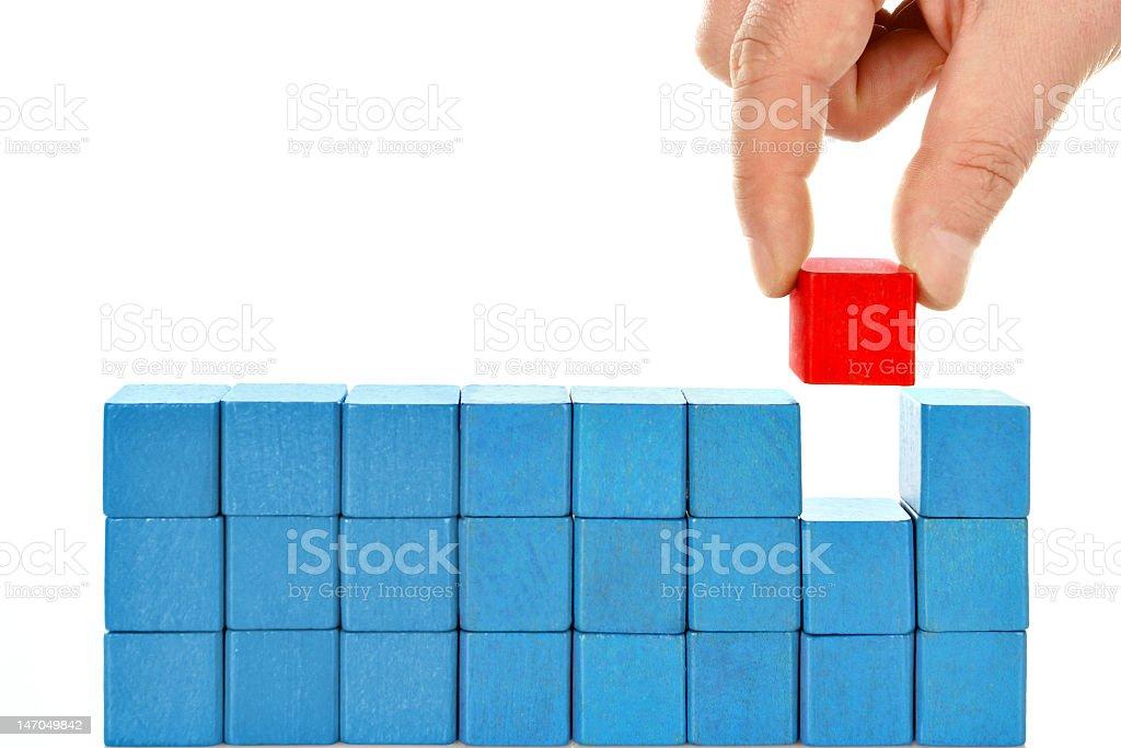 Fire-engine red cube amongst vibrant blue building blocks stock photo