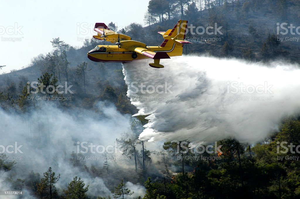 A firefighter airplane putting out a forest fire stock photo