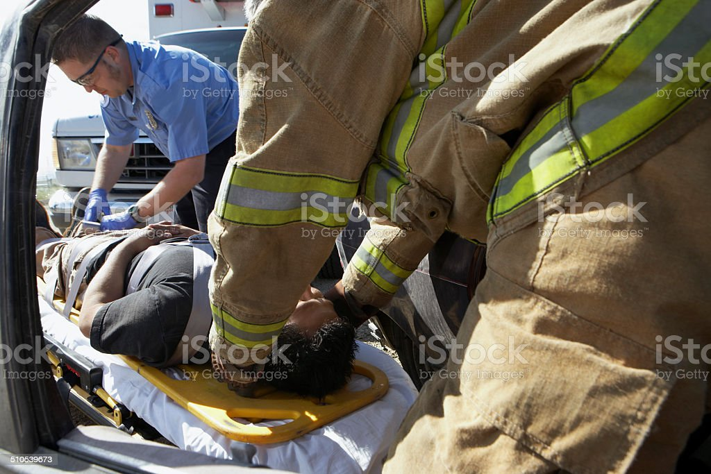 Firefighter and paramedics taking victim out of crashed car stock photo