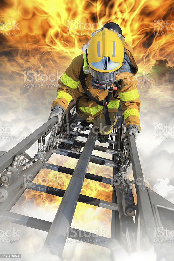 Firefighter ascends upon a one hundred foot ladder. stock photo