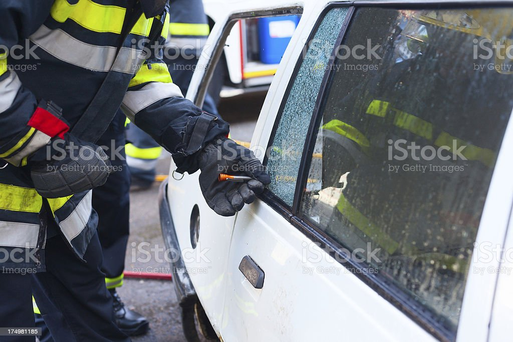 Firefighter breaks glass on car royalty-free stock photo