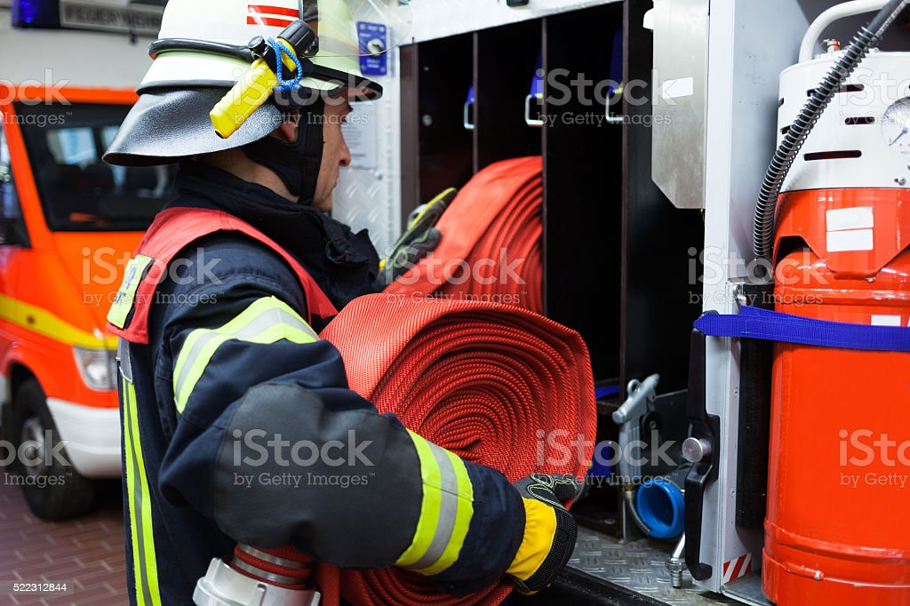 Firefighter carrying a fire hose stock photo