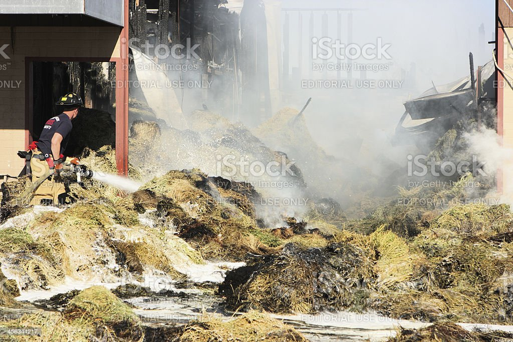 Firefighter Extinguishes Burning Fire Smoke royalty-free stock photo