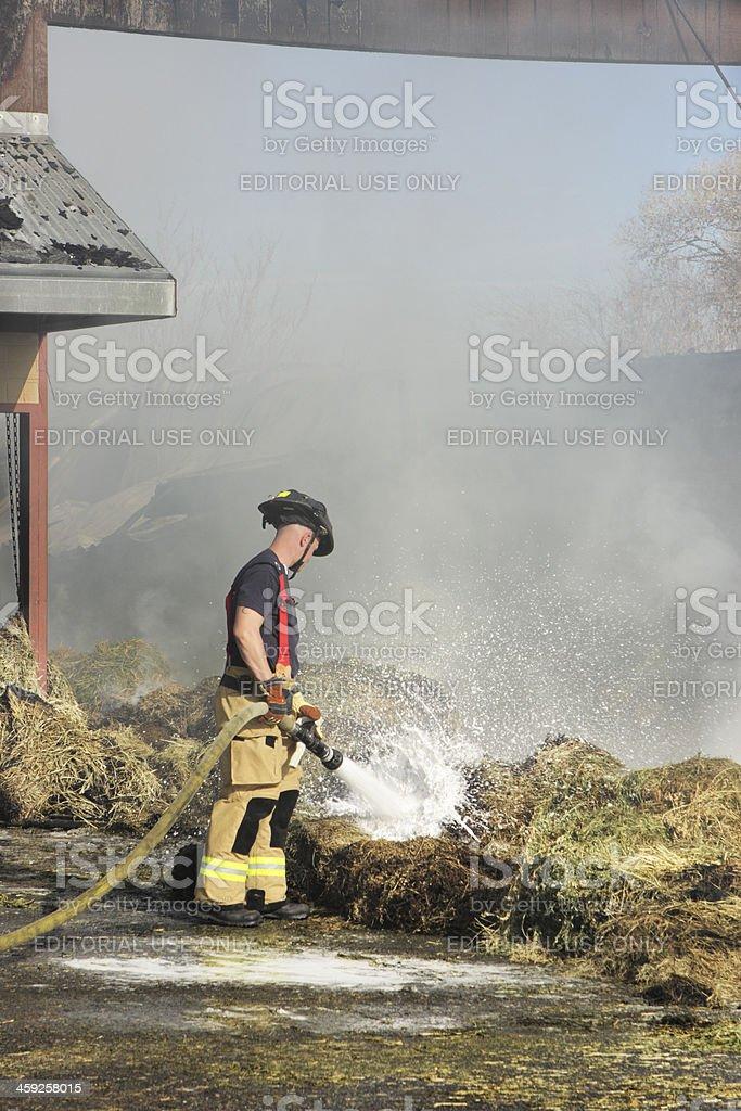 Firefighter Extinguishes Burning Hay royalty-free stock photo