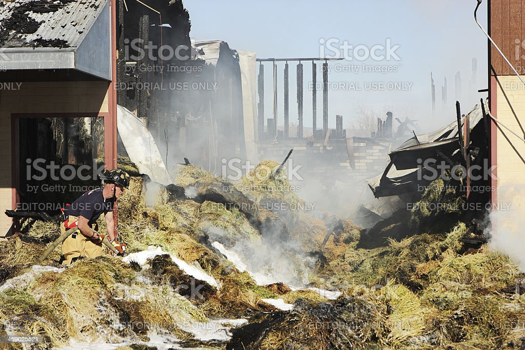 Firefighter Extinguishes Fire Using Firehouse royalty-free stock photo