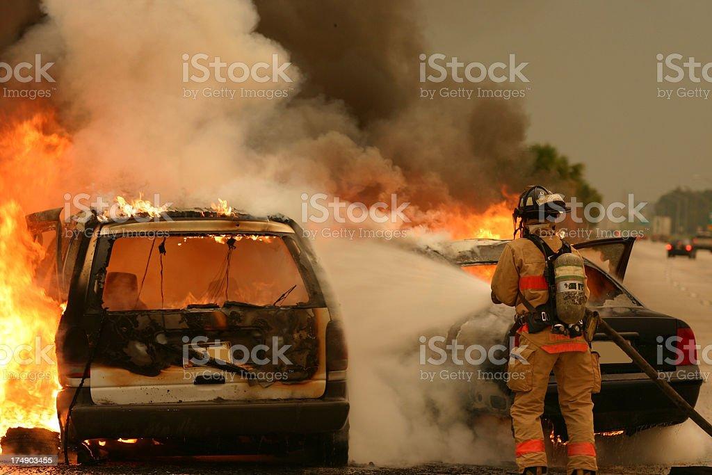 Firefighter extinguishing burning vehicle stock photo