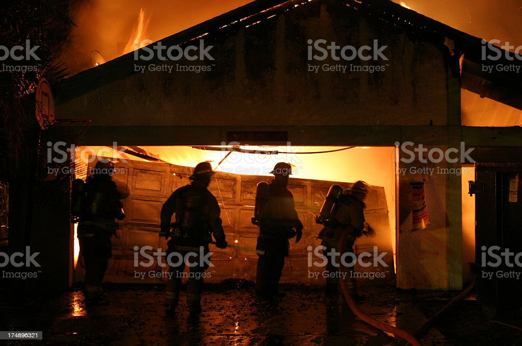 Firefighter fighting a house fire stock photo