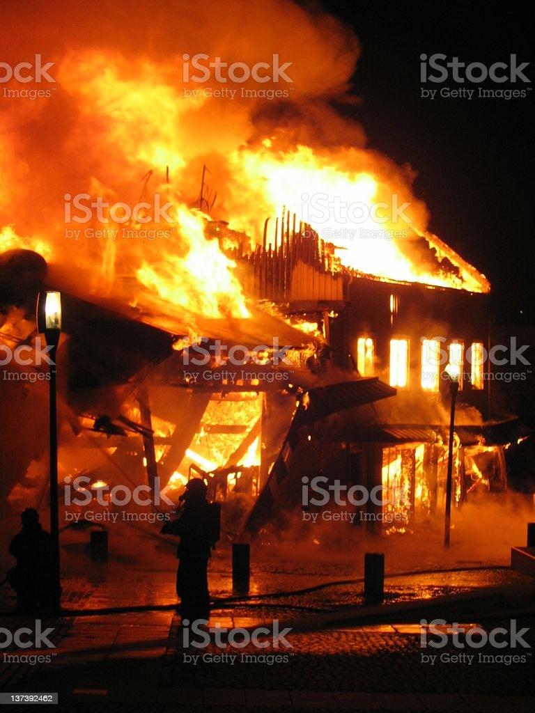 Firefighter fighting burning house. stock photo