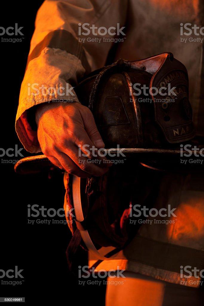 Firefighter holding helmet stock photo