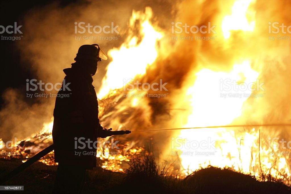Firefighter Holding Hose Pointing Water Stream onto Fire stock photo