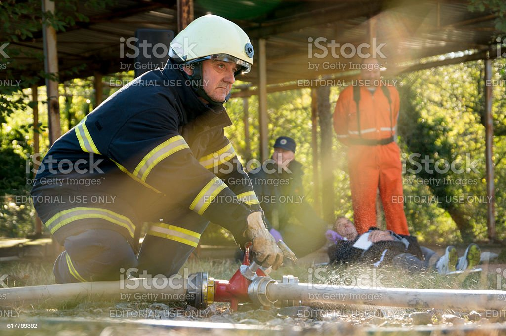 Firefighter in action with rescue team behind him stock photo