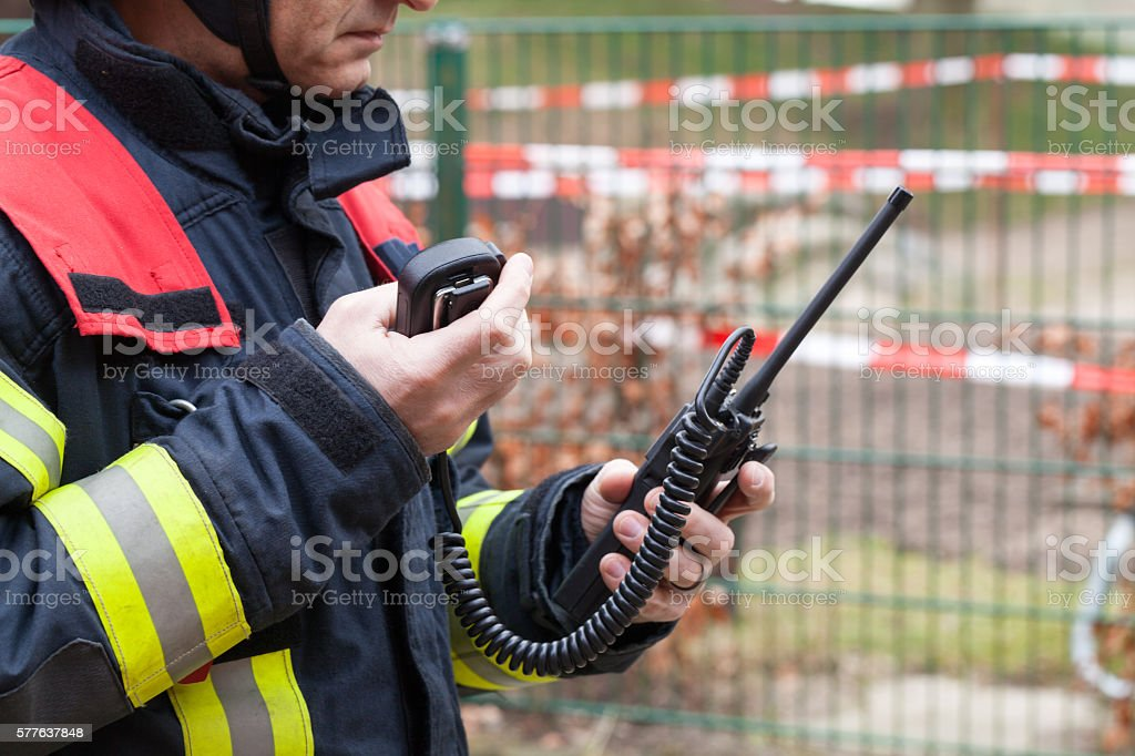 Firefighter in action with walkie takie in the hand stock photo