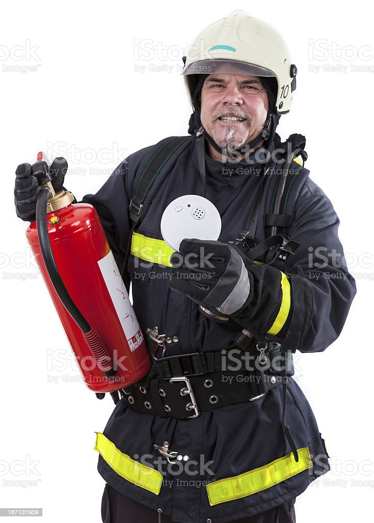 firefighter is showing a smoke detector and extinguisher royalty-free stock photo