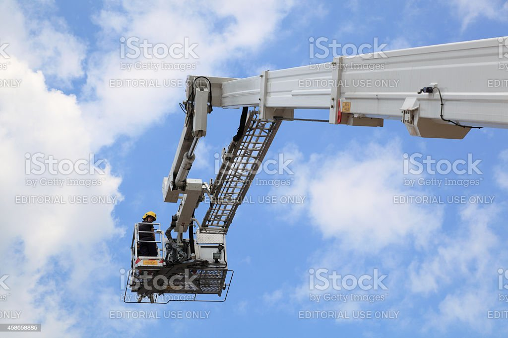 firefighter operates a hydraulic rescue lift against blue sky stock photo