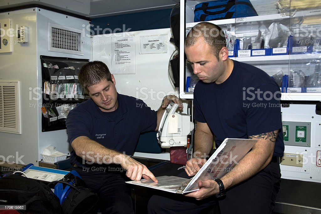 Firefighter paramedics checking equipment in ambulance. Emergency, medical, technician. stock photo