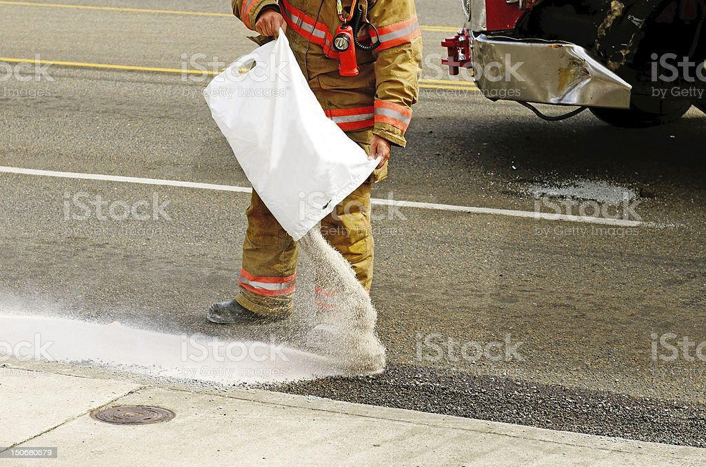 Firefighter pouring absorb any on oil spilled from a wreck stock photo
