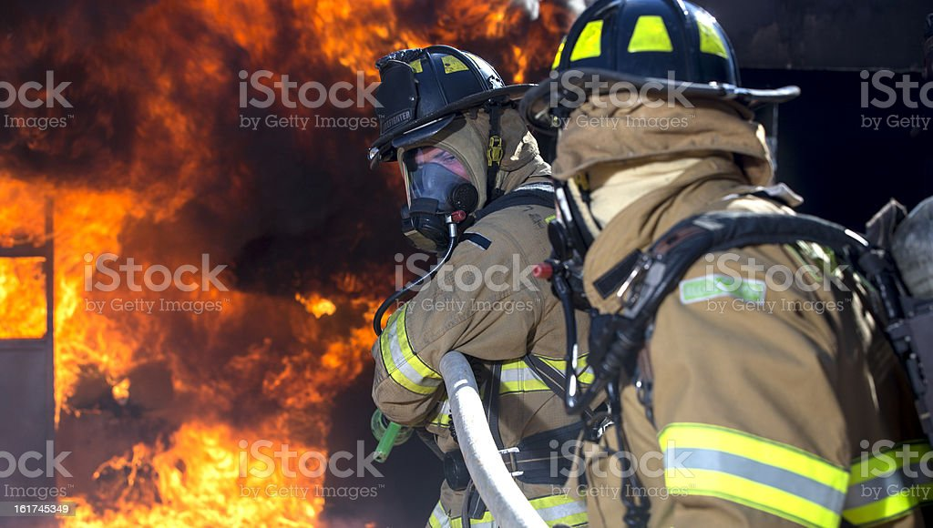 Firefighter ready to spray water royalty-free stock photo