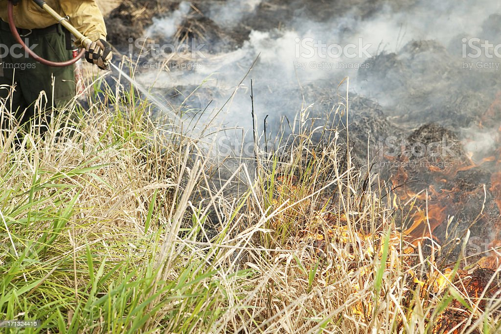Firefighter Spraying a Prairie Grass Fire royalty-free stock photo