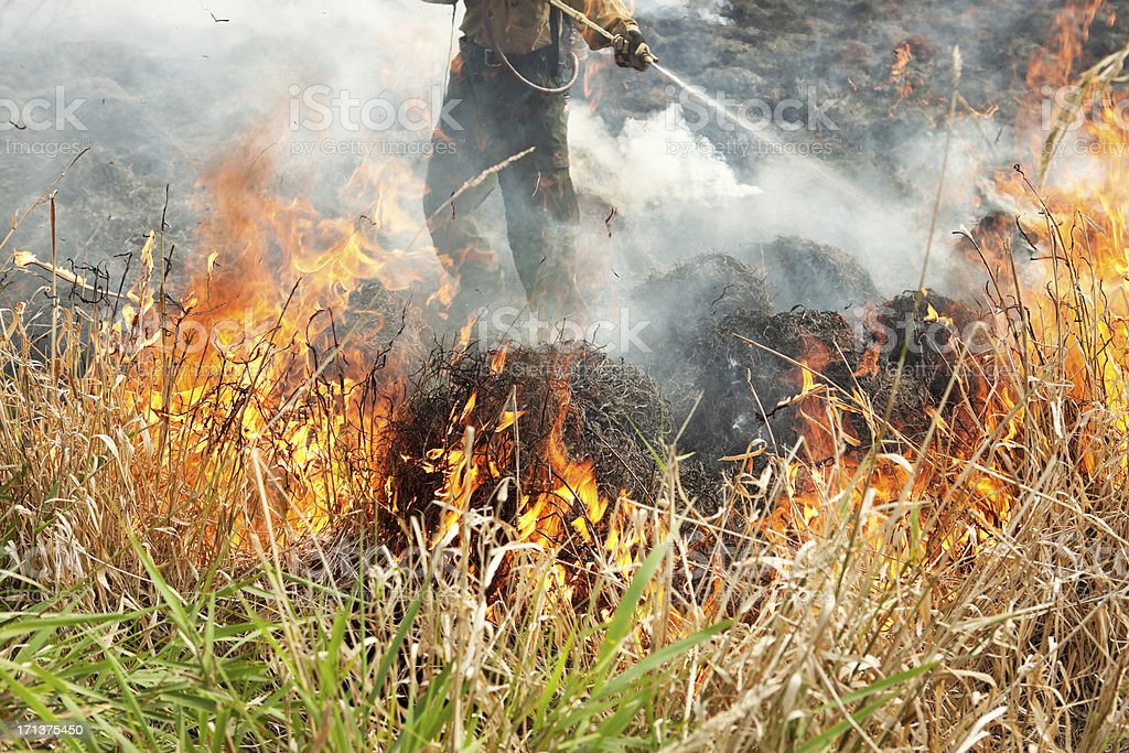 Firefighter Spraying a Prairie Grass Fire royalty-free stock photo