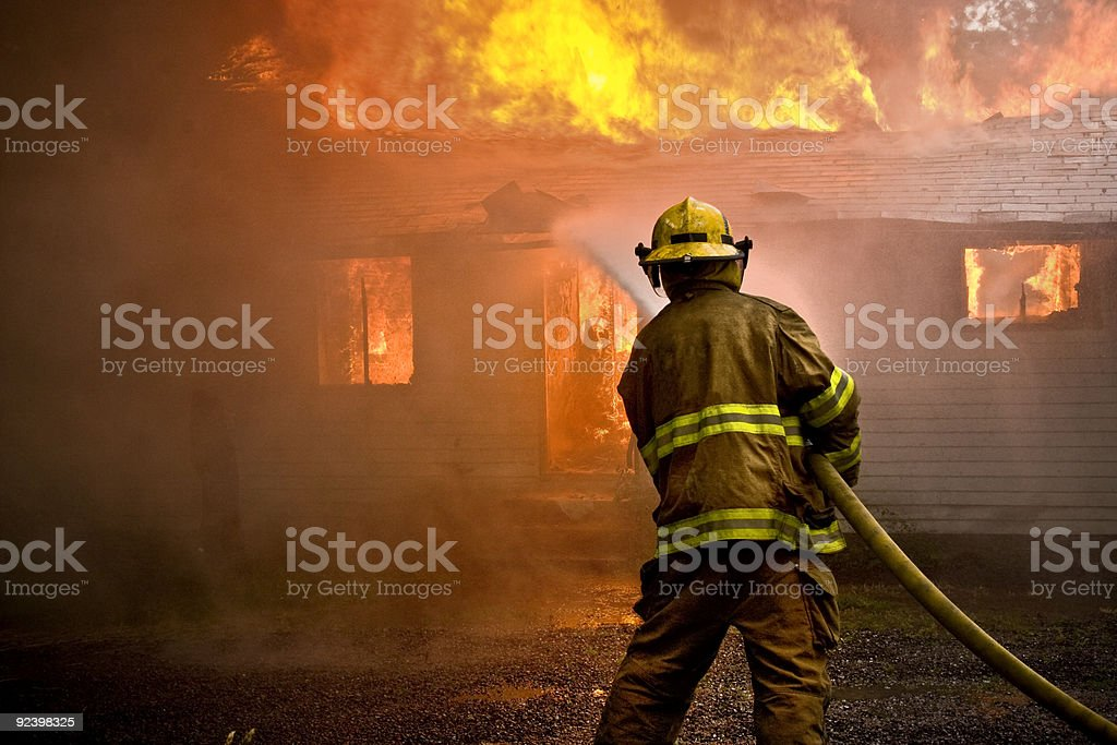 Firefighter spraying water at a house fire stock photo