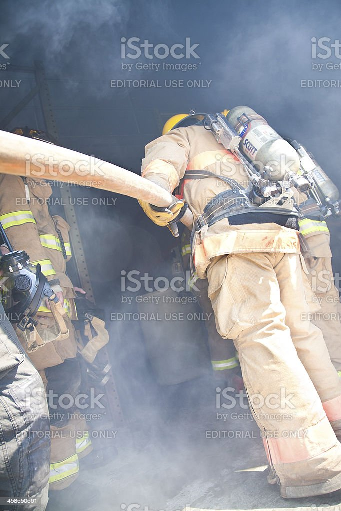 Firefighter Using Hose to Put Out Fire in Building stock photo