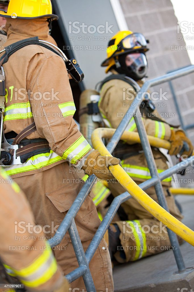 Firefighter trainees bringing in fire hose into burning building...