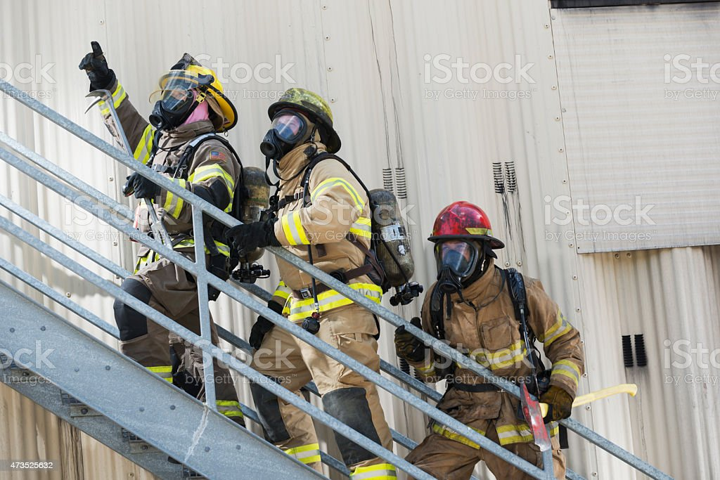 Firefighters climbing stairs outside industrial building stock photo