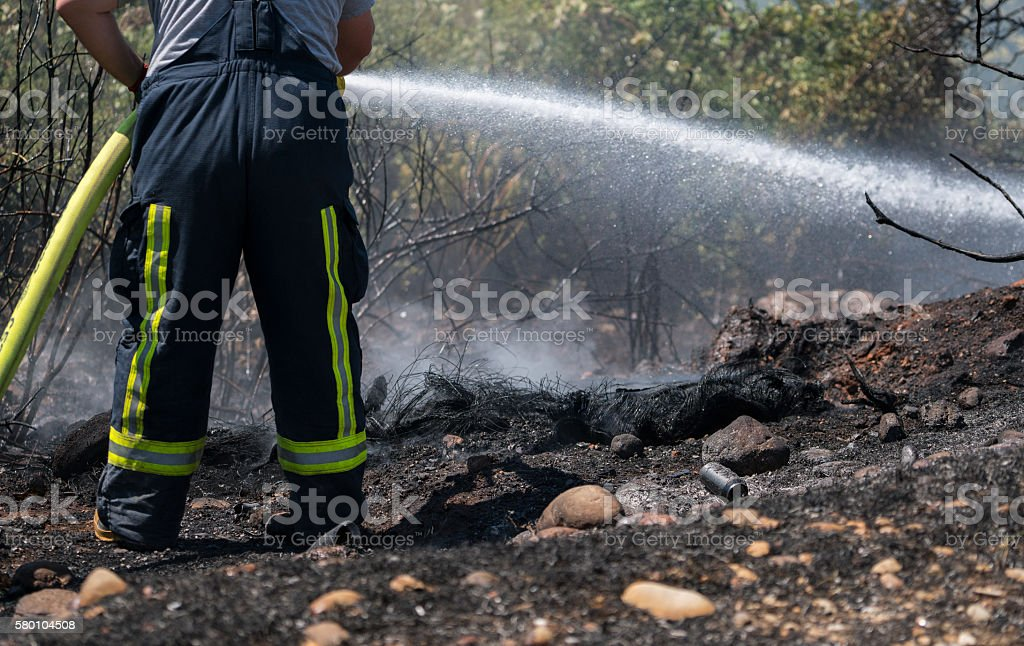 Firefighters cooling the field fire stock photo
