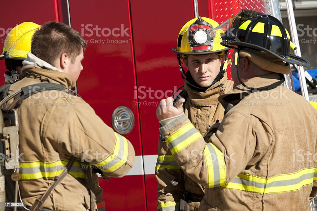 Firefighters Discussing Operational Procedures In Front of Firetruck stock photo