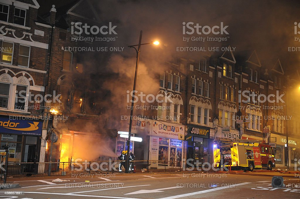 Firefighters douse fire after London riots stock photo