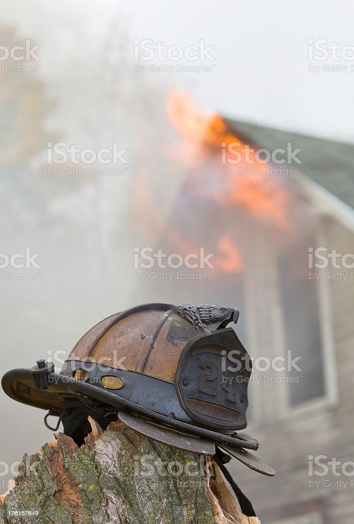 Firefighter's Helmet Near House Fire royalty-free stock photo