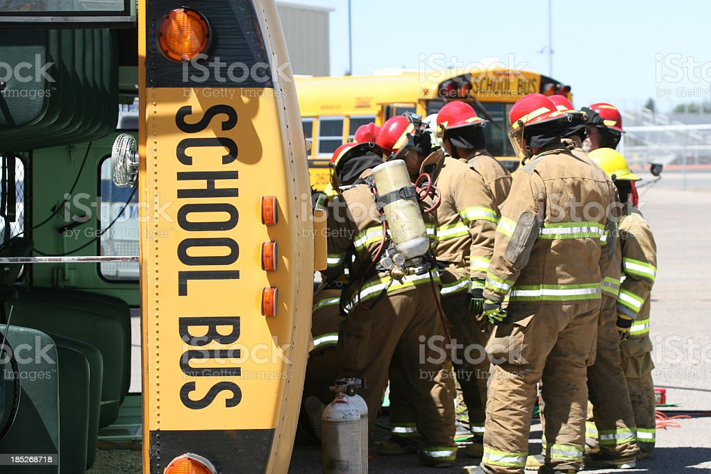 Firefighters helping at a school bus accident royalty-free stock photo