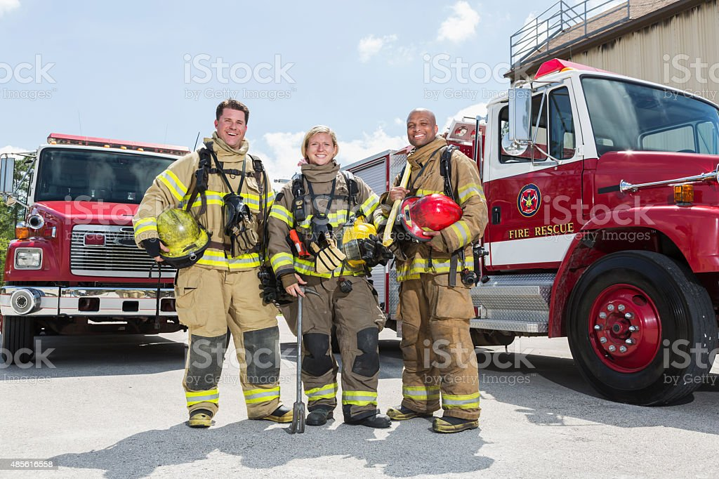 Firefighters in protective gear with fire rescue trucks stock photo