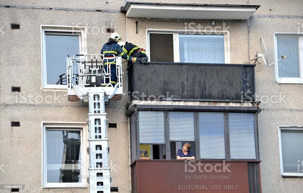 Firefighters into telescopic boom basket try to get to balcony. stock photo
