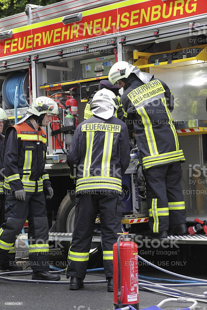 Firefighters pack and check equipment in firetruck stock photo